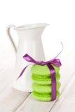 Зеленые macarons с фиолетовым кувшином ленты и молока Стоковая Фотография RF