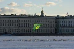 Зеленый змей летая над рекой Neva напротив embank дворца Стоковое Фото
