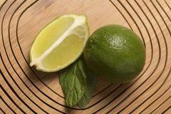 Зеленый лимон и минута на деревянной предпосылке Стоковая Фотография