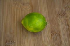 Зеленый лимон на деревянной доске Стоковое фото RF