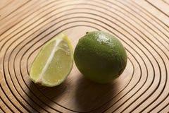 Зеленый лимон на деревянной предпосылке Стоковая Фотография