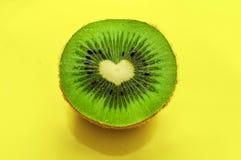 Зеленый киви в форме сердца на желтой предпосылке Стоковая Фотография