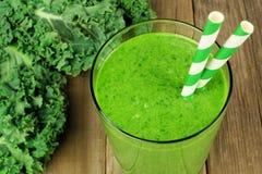 Зеленый конец smoothie листовой капусты вверх на деревянной предпосылке Стоковое Изображение