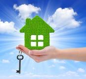 Зеленый дом с ключом в руке Стоковые Изображения RF