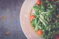 Зеленый салат с томатами и гайки сосны metal предпосылка Стоковые Фотографии RF