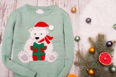 Зеленый свитер с медведем на деревянной предпосылке вал ели украшений рождества ветви Взгляд сверху Стоковые Фотографии RF