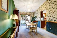 Зеленый семейный номер с флористическими обоями, коричневым шкафом и полом ковра Стоковое Фото