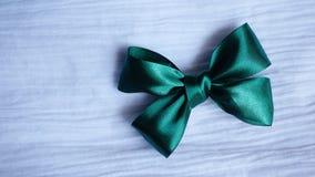 Зеленый смычок ленты на белой предпосылке ткани стоковое фото rf