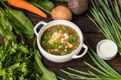 Зеленый суп с яичками и ингридиентами для его варить Деревянная предпосылка Взгляд сверху Конец-вверх стоковое фото rf