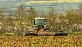 Зеленый трактор в поле культивируя почву стоковая фотография rf