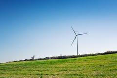 Зеленый луг при ветротурбины производя электричество стоковое изображение