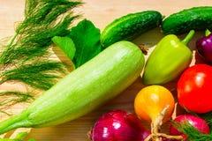 Зеленый укроп, фиолетовый лук перцев, томатов, цукини, голубых и желтых на деревянной предпосылке в солнечном свете Стоковая Фотография RF