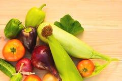 Зеленый, фиолетовый лук перцев, томатов, мозоли, цукини, голубых и желтых на деревянной предпосылке в отраженном свете Стоковые Фотографии RF