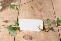 Зеленый цвет выходит с пустой биркой на деревянную предпосылку стоковая фотография