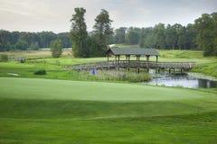 Зеленый цвет поля для гольфа с мостом и прудом в предпосылке Стоковые Фотографии RF