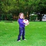 зеленый цвет травы девушки шарика предпосылки меньшее играя временя Стоковое фото RF