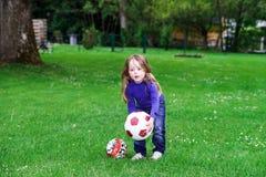 зеленый цвет травы девушки шарика предпосылки меньшее играя временя стоковые изображения