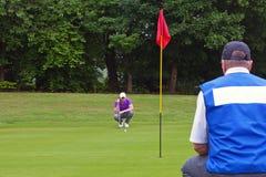 Зеленый цвет установки игрока в гольф и caddy. Стоковое фото RF