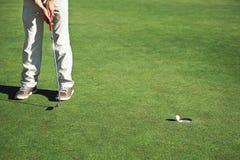 Зеленый цвет удар, загоняющий мяч в лунку гольфа Стоковое Изображение