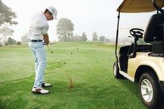 Зеленый цвет удар, загоняющий мяч в лунку гольфа Стоковое Изображение RF