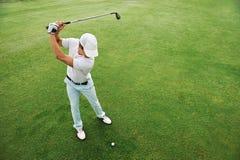 Зеленый цвет удар, загоняющий мяч в лунку гольфа Стоковые Фотографии RF