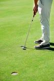 Зеленый цвет удар, загоняющий мяч в лунку гольфа Стоковое фото RF