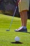 Зеленый цвет удар, загоняющий мяч в лунку гольфа стоковые фото