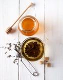 Зеленый чай в стеклянных блюде, сахаре, имбире и меде на белой предпосылке стоковая фотография rf