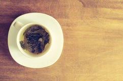 Зеленый чай и листья на деревенском деревянном столе Стоковое Изображение