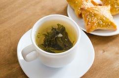 Зеленый чай и пироги на деревенском деревянном столе Стоковые Фото
