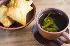 Зеленый чай и пироги на деревенском деревянном столе Стоковая Фотография