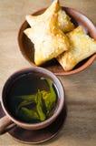 Зеленый чай и пироги на деревенском деревянном столе Стоковая Фотография RF