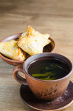 Зеленый чай и пироги на деревенском деревянном столе Стоковые Изображения