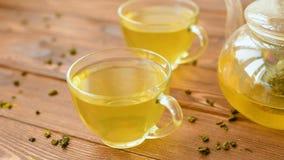 Зеленый чай с мятой, поднял, ягоды goji и ананас в чайнике сток-видео