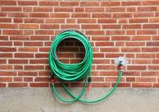 Зеленый шланг воды вися красную кирпичную стену Стоковая Фотография RF