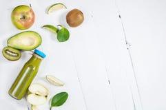 Зеленый smoothie в bottl с авокадоом, яблоком и кивиом на белой деревянной предпосылке Стоковое фото RF