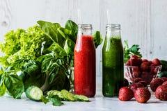 Зеленый smoothie и smoothie клубники в 2 малых бутылках с ингридиентами на светлой деревянной предпосылке Здоровый вытрезвитель Стоковые Изображения RF