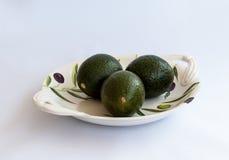 3 зеленых авокадоа лежат на плите фарфора декоративной покрашенной Стоковое Изображение RF