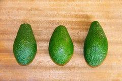 3 зеленых авокадоа на деревянной предпосылке Стоковое Изображение RF