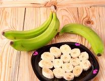 2 зеленых бананы и куска в плите на деревянной предпосылке Стоковое фото RF