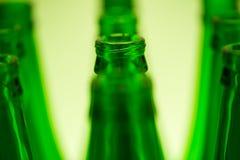 10 зеленых бутылок в 3 строках сняли с зеленым светом Стоковое Изображение RF