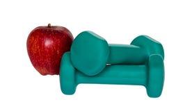 2 зеленых гантели и красного яблоко изолированные на белой предпосылке Стоковые Изображения