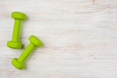 2 зеленых гантели на деревянной предпосылке с космосом экземпляра Стоковые Фото
