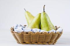 3 зеленых груши в корзине на деревянной белой таблице Стоковая Фотография