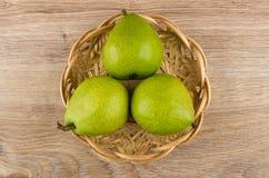 3 зеленых груши в плетеной корзине на деревянном столе Стоковые Фотографии RF