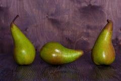 3 зеленых груши на деревянной коричневой таблице Стоковое фото RF