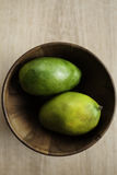 2 зеленых зрелых манго в деревянном шаре Стоковое Фото