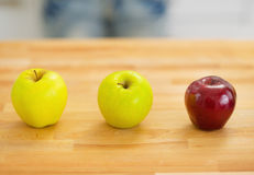 2 зеленых и одних красных яблока на разделочной доске Стоковые Фотографии RF