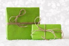 2 зеленых подарка на снеге, влиянии Bokeh Стоковое Изображение