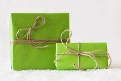 2 зеленых подарки или настоящего момента на снеге, белой предпосылке Стоковая Фотография RF